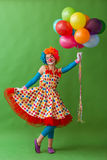 Funny playful clown. Funny playful female clown in colorful wig holding balloons, posing, looking at camera and smiling, standing on a green background Stock Image