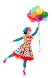 Funny playful clown. Funny playful female clown in colorful wig holding balloons, standing on one leg like ready to fly, isolated on a white background Stock Photo