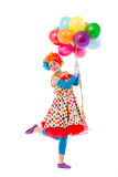 Funny playful clown. Funny playful female clown in colorful wig holding balloons, standing on one leg, looking at camera and smiling, isolated on a white Royalty Free Stock Images