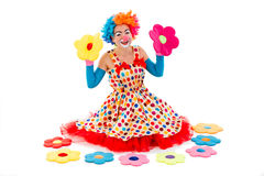 Funny playful clown. Funny playful female clown in colorful wig holding toy flowers in both hands, looking at camera and smiling, sitting near toy flowers Stock Photo