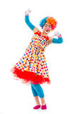 Funny playful clown. Funny playful female clown in colorful wig showing not OK sign, looking at camera and smiling, isolated on a white background Royalty Free Stock Photography