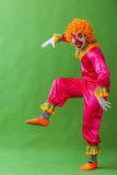 Funny playful clown. In orange wig imitating, looking at camera and smiling, standing on a green background Royalty Free Stock Photo