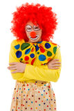 Funny playful clown. Portrait of a funny angry or offended clown in red wig looking at camera, isolated on a white background Royalty Free Stock Photos