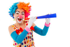 Funny playful clown. Portrait of a funny playful female clown in colorful wig blowing horn, looking at camera and smiling, isolated on a white background Stock Images