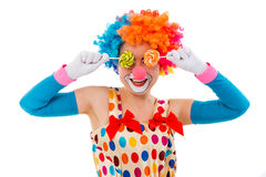 Funny playful clown. Portrait of a funny playful female clown in colorful wig covering eyes with lollipops and smiling, isolated on a white background Royalty Free Stock Images