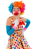 Funny playful clown. Portrait of a funny playful female clown in colorful wig covering mouth with lips lollipops and looking at camera, isolated on a white Stock Images