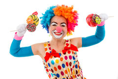 Funny playful clown. Portrait of a funny playful female clown in colorful wig holding lollipops in both hands, looking at camera and smiling, isolated on a white Stock Photography