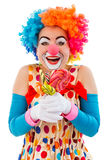 Funny playful clown. Portrait of a funny playful female clown in colorful wig holding lollipops, looking at camera and smiling, isolated on a white background Royalty Free Stock Photos