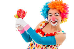 Funny playful clown. Portrait of a funny playful female clown in colorful wig holding lollipops, looking at camera and smiling, isolated on a white background Royalty Free Stock Photo
