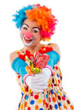 Funny playful clown. Portrait of a funny playful female clown in colorful wig holding lollipops, looking at camera and smiling, isolated on a white background Stock Photography