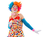 Funny playful clown. Portrait of a funny playful female clown in colorful wig holding a pink bow tie on stick and looking at camera, isolated on a white Stock Photo
