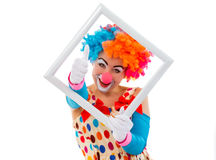 Funny playful clown. Portrait of a funny playful female clown in colorful wig holding a white frame, looking at camera and showing OK sign, isolated on a white Stock Images