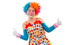 Funny playful clown. Portrait of a funny playful female clown in colorful wig showing OK sign, looking at camera and smiling, isolated on a white background Royalty Free Stock Image