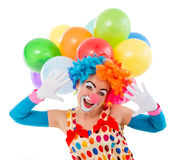 Funny playful clown. Portrait of a funny playful female clown in colorful wig teasing, looking at camera and showing palms, in the background balloons, isolated Stock Photography