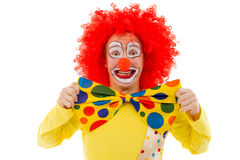 Funny playful clown. Portrait of a funny playful clown in red wig adjusting his big colorful bow tie, looking at camera and smiling, isolated on a white Royalty Free Stock Image