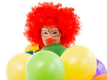 Funny playful clown. Portrait of a funny playful clown in red wig with balloons looking at camera, isolated on a white background, close-up Stock Images