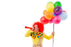 Funny playful clown. Portrait of a funny playful clown in red wig blowing horn, holding balloons, looking at camera and smiling, isolated on a white background Royalty Free Stock Photography