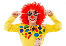 Funny playful clown. Portrait of a funny playful clown in red wig covering his eyes with lollipops and smiling, isolated on a white background Stock Image