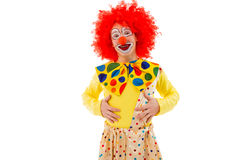 Funny playful clown. Portrait of a funny playful clown in red wig keeping hands on stomach, looking at camera and smiling, isolated on a white background Stock Photo
