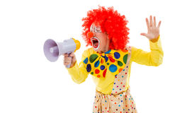 Funny playful clown. Portrait of a funny playful clown in red wig screaming into loudspeaker, isolated on a white background Royalty Free Stock Photos