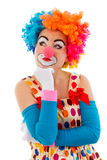 Funny playful clown. Portrait of a funny thoughtful female clown in colorful wig keeping hand on chin and looking away, isolated on a white background Royalty Free Stock Image
