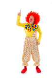 Funny playful clown. In red wig pointing and looking upwards, isolated on a white background Stock Photos