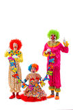 Funny playful clown. Three funny playful clowns holding Happy birthday garland, looking at camera and smiling isolated on a white background. Woman sitting, men Royalty Free Stock Photo