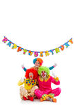 Funny playful clown. Three funny playful clowns showing OK sign, in the background hanging Happy birthday garland, isolated on a white Stock Image