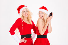 Funny playful sisters twins in santa claus dresses and hats Royalty Free Stock Images