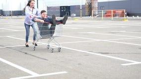 Woman pushing boyfriend sitting in shopping cart stock video footage