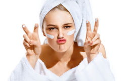 Funny playful young woman in white bathrobe applying moisturizer and making duck face over white background. royalty free stock image
