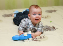 Funny pleased little boy lying on the bed with his toy. At home Stock Photo