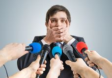 Funny politician is making no comment gesture. Many microphones in front Royalty Free Stock Photo