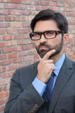 A funny pondering businessman with glasses Royalty Free Stock Photo