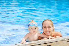 Funny portrait of baby boy swimming with mother in pool Royalty Free Stock Photo