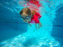 Funny portrait of baby girl swimming and diving in blue pool stock image