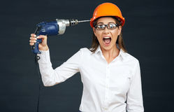 Funny portrait of business woman builder drills his head. Royalty Free Stock Photo