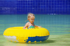Funny portrait of cheerful baby girl swimming in water park Royalty Free Stock Images