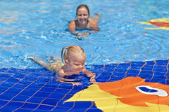 Funny portrait of cheerful baby girl swimming in water park Stock Photography