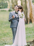 The funny portrait of the cheerful newlyweds spending time in the park. stock photography