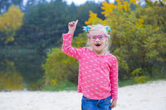 Funny portrait of emotional girl in pink glasses. Amusing wriggling girl in pink glasses outdoors Royalty Free Stock Photography