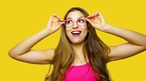 Funny portrait of excited girl wearing glasses eyewear. Closeup portrait of young woman making funny face expression  on. Yellow background. Beautiful young stock photography