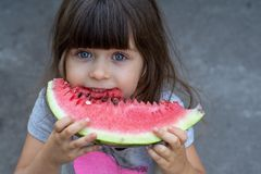 Funny portrait of an incredibly beautiful little girl blue eyes, eating watermelon, healthy fruit snack stock image