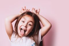 Funny portrait of little girl on pink background. Emotional child portrait. Copyspace for text stock photography
