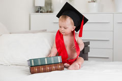 Funny portrait of 10 months baby in graduation cap looking at bi Royalty Free Stock Photography