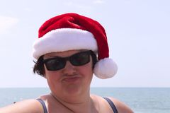 Funny portrait of a overweight woman in a santa hat and sunglasses against the background of the sea. stock photography