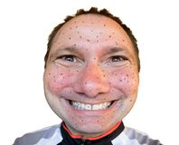 Funny portrait of sweaty biker with flies stuck to his face Stock Photo