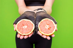 Funny portrait of young brunette fitness woman holding fresh pink grapefruit. Healthy eating lifestyle and weight loss concept. Royalty Free Stock Photos