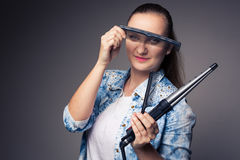 Funny portrait of a young female hairstylist. Holding her tools and posing with a comb in front of her eyes ion front of a grey backdrop (color toned image Stock Photography