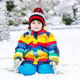 Funny preschool boy in colorful clothes happy about snow, outdoo Royalty Free Stock Photography